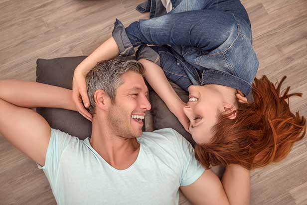 Mann und Frau auf beheiztem Fußboden: Angebot für Ihre Heizung anfordern